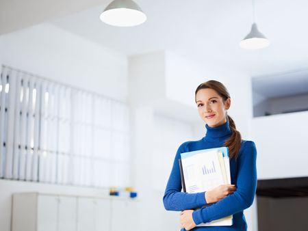 business woman: business woman holding reports and looking at camera. Copy space