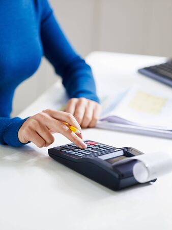 woman typing: close up of business woman typing on calculator