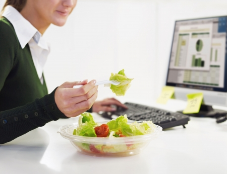 eating in: cropped view of woman eating salad in office. Copy space