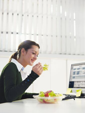 woman eating salad in office. Copy space Stock Photo - 6054685