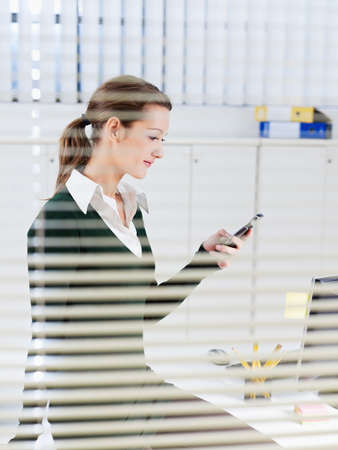 woman using mobile phone in office photo
