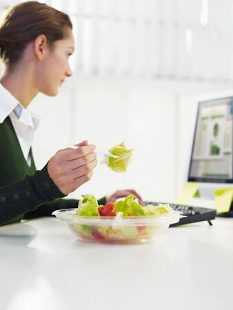 woman eating salad in office. Copy space Stock Photo - 6074536
