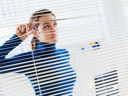 young businesswoman looking through blinds. Copy space photo