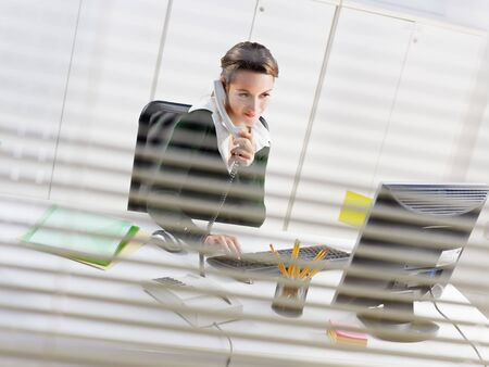 woman talking on mobile phone in office photo