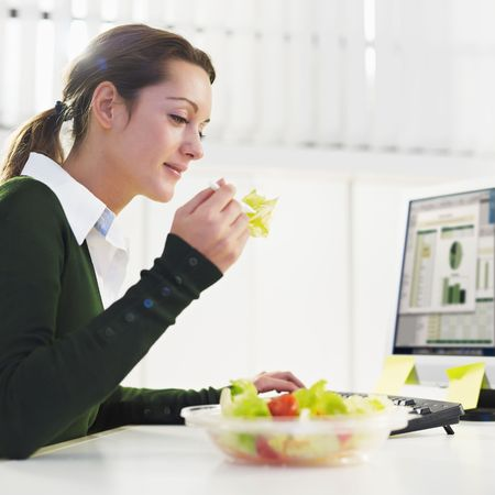 lunch break: woman eating salad in office. Copy space Stock Photo