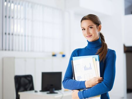 business woman holding reports and looking at camera. Copy space photo
