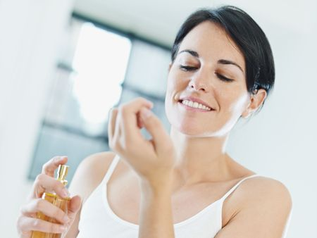 wrist: woman putting on perfume and smiling. Copy space