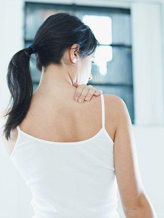 woman massaging neck. Rear view photo