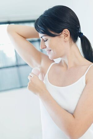 armpit hair: donna messa su deodorante stick e sorridente. Vista laterale