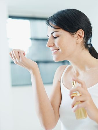 fragrance: woman putting on perfume and smiling. Copy space