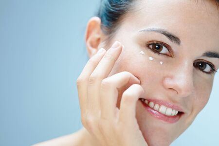 woman face cream: close up of woman applying eye cream Stock Photo