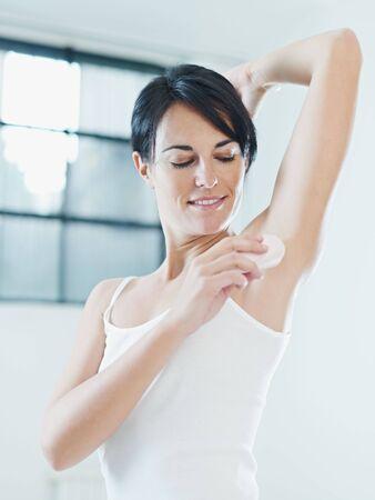 armpit: mujer poniendo en Palo desodorante y sonriente.