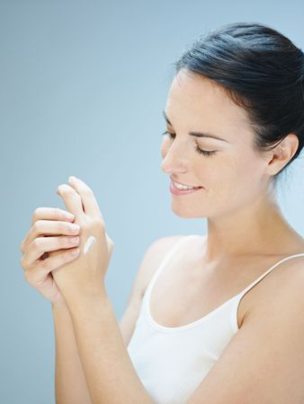 Woman putting cream on hands. Copy space photo