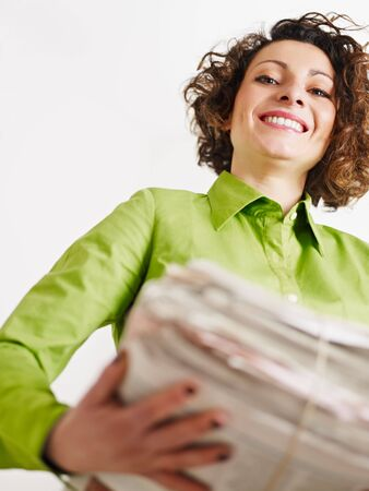 woman holding newspapers for recycling. Copy space photo