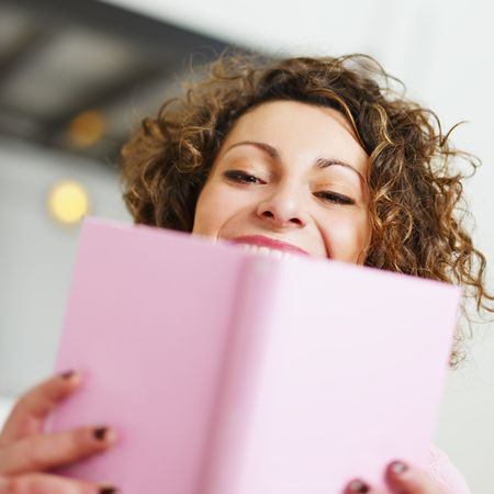 woman reading book at home and laughing. Copy space Stock Photo - 6156097