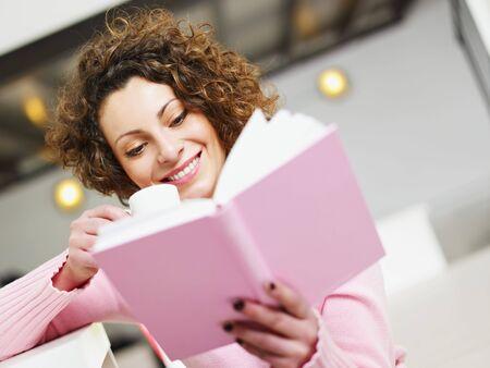 mujer leyendo libro: Mujer leyendo el libro en casa y beber caf�. Copiar el espacio
