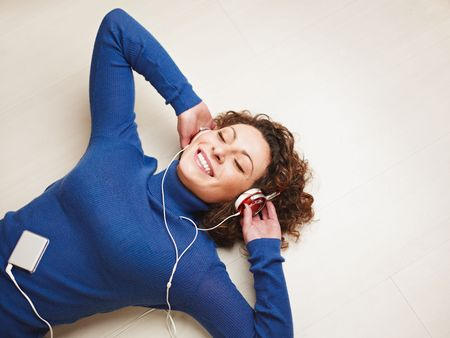 listening to people: woman lying on floor and listening to music. Copy space Stock Photo