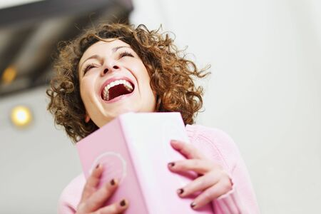 woman reading book at home and laughing. Copy space