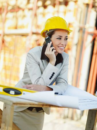 female architect talking on mobile phone in construction site photo