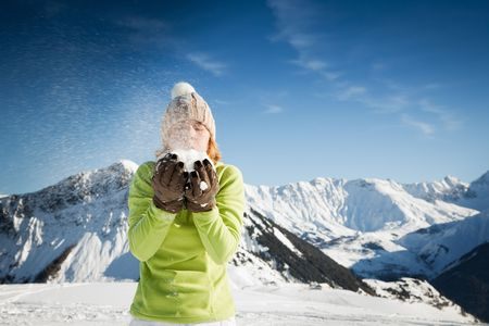 woman blowing on snow outdoors. Copy space