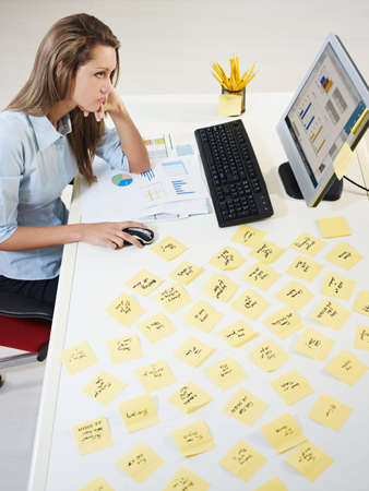 schedule reports: tired business woman with adhesive notes on table. High angle view