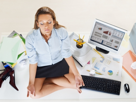 meditating: stressed businesswoman doing yoga in office. High angle view, copy space