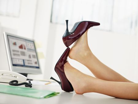 business woman taking off shoes in office. photo
