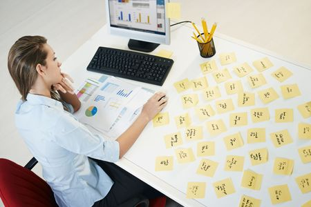 high angle: tired business woman with adhesive notes on table. High angle view