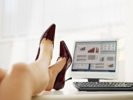 female feet: business woman taking off shoes in office. Copy space