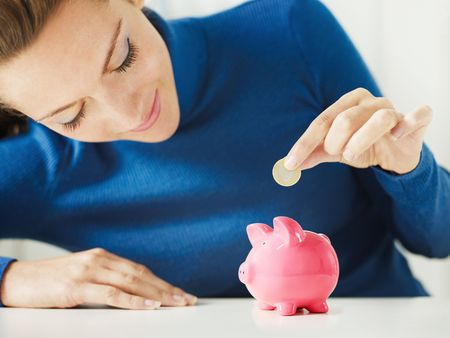 woman putting 1 euro in small piggy bank. Selective focus, Copy space photo