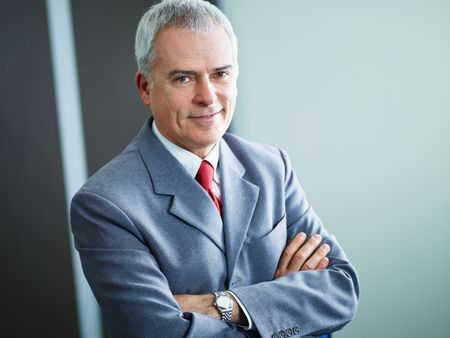 one senior adult man: portrait of mature business man with arms folded, looking at camera. Copy space Stock Photo