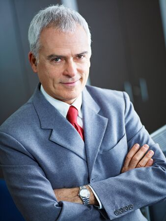 portrait of mature business man with arms folded, looking at camera. Copy space photo