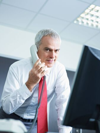 portrait of mature business man talking on the phone, looking at camera. Copy space Stock Photo - 6309683
