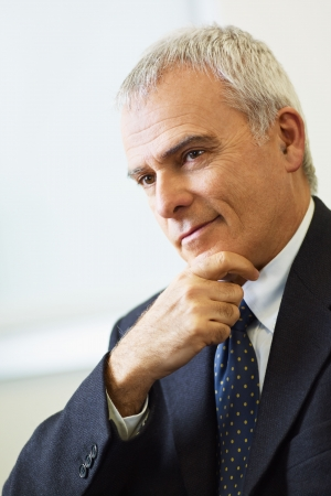 portrait of mature business man with hand on chin, looking away. Copy space photo
