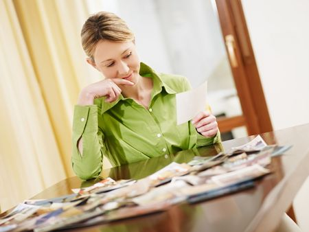 mid adult woman looking at pictures at home. Copy space photo