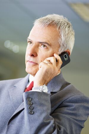 portrait of mature business man talking on the phone, looking away. Stock Photo - 6341011