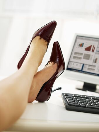 feet on desk: business woman taking off shoes in office. Stock Photo