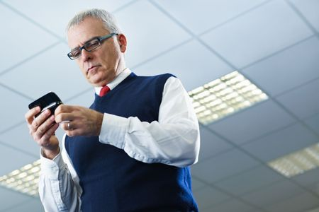 portrait of mature business man typing on mobile phone. Low angle view, Copy space photo