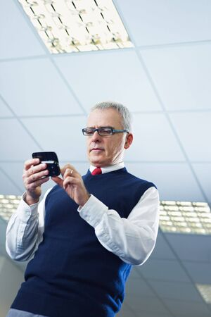portrait of mature business man typing on mobile phone. Low angle view, Copy space Stock Photo - 6351516