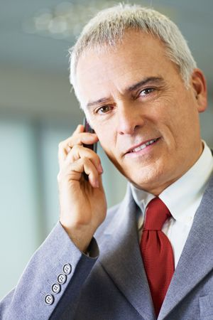 portrait of mature business man talking on the phone, looking at camera and smiling. photo