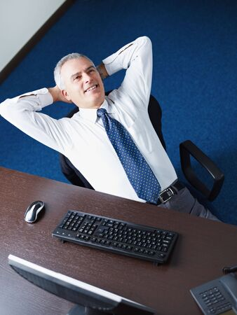 Mature business man leaning on chair with hands behind head, looking away and smiling. Copy space photo