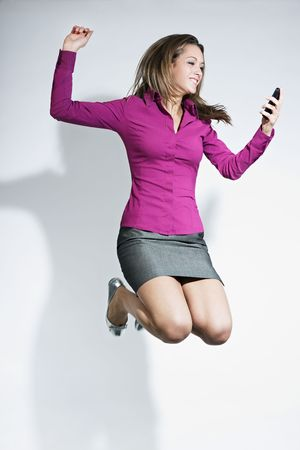 businesswoman skirt: happy business woman holding cellphone and jumping for joy. Copy space