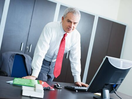 portrait of mature business man leaning on desk, looking at camera. Copy space photo