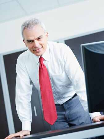 portrait of mature business man leaning on desk, looking at camera. Copy space Stock Photo - 6351522