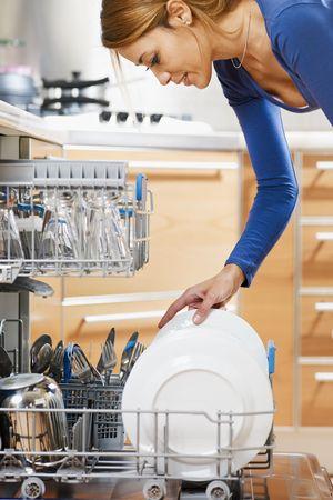 everyday scenes: vista laterale della giovane donna in cucina facendo housework