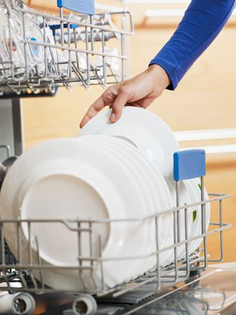 close up of woman in kitchen using dishwasher photo