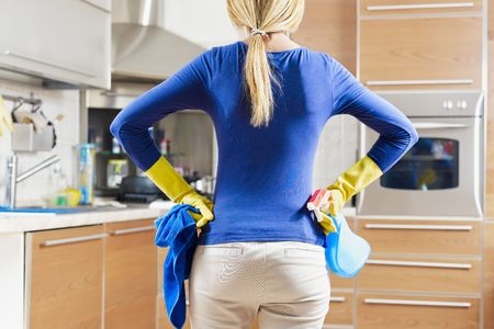rear view of woman with yellow gloves in kitchen doing housework photo
