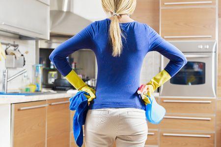 everyday scenes: retrovisiva di donna con i guanti gialli in cucina, facendo lavori domestici Archivio Fotografico