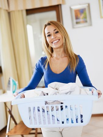 laundry: woman holding basket of laundry and looking at camera Stock Photo