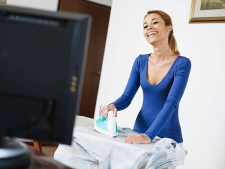 woman ironing: woman with iron, watching tv show and laughing Stock Photo